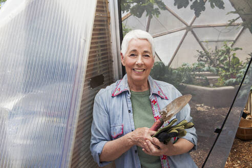 Smiling senior woman gardening in a geodesic dome, climate controlled glass house - MINF15208