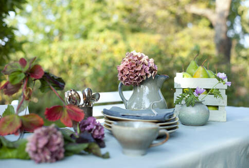 Crockery,DIYlamp shade and jug with blooming hydrangeas lying on coffee table set in garden - GISF00670