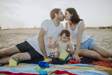 Husband and wife kissing while son playing with toys at beach - GMLF00736