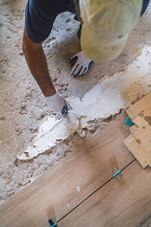 High angle view of male manual worker laying cement on parquet floor in house - SNF00681
