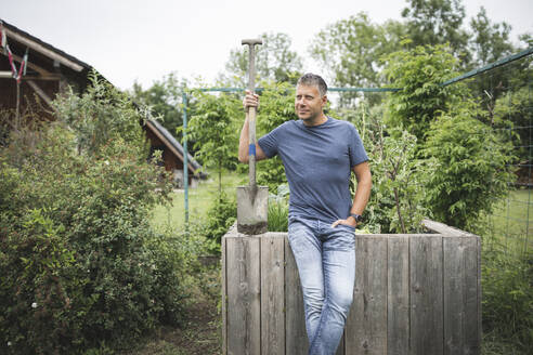 Handsome man holding spade looking away while leaning on wooden raised bed at vegetable garden - HMEF01079