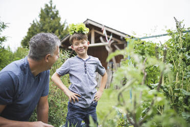 Playful boy with plant on head looking at father in garden - HMEF01100