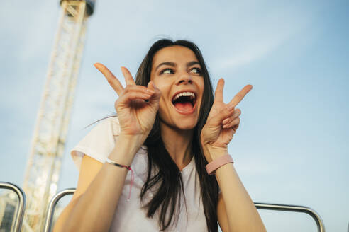 Cheerful young woman showing peace sign while enjoying Ferris wheel ride at sunset - OYF00222