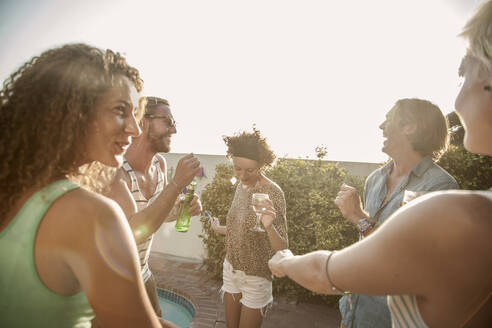 Happy friends dancing while enjoying pool party at sunset - AJOF00294