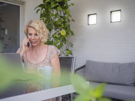 Smiling blond businesswoman talking on phone while sitting with laptop working at home - LAF02496