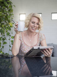 Smiling female entrepreneur holding laptop and coffee cup while working at home office - LAF02502