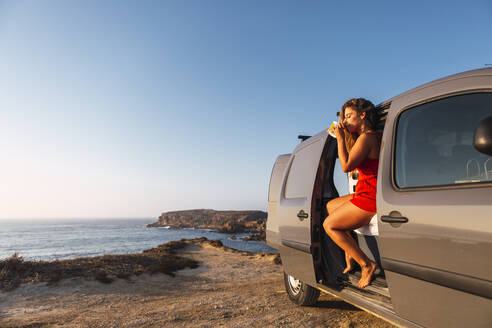 Woman drinking coffee while sitting in camper van at beach - DCRF00968
