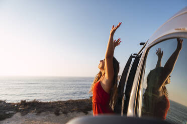 Young woman with hand raised standing by camper van at beach - DCRF00971