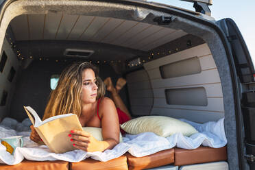Woman with book looking away while lying in camper van at beach - DCRF00974