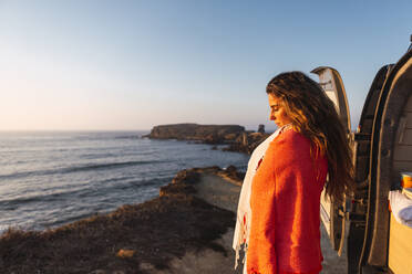 Woman with eyes closed covering shawl while standing at beach - DCRF00983