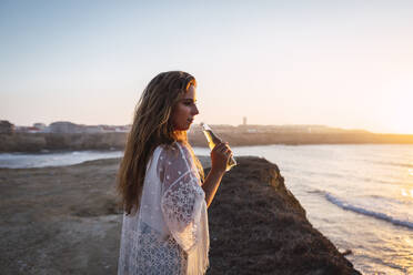 Young woman with small white wine bottle looking away while standing at beach - DCRF00989