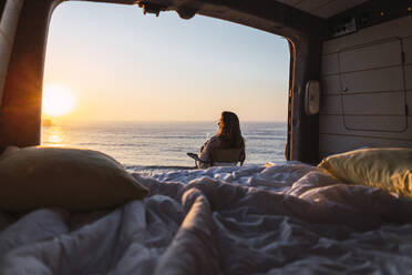 Woman admiring sunset view while while sitting on chair by camper van at beach - DCRF00992