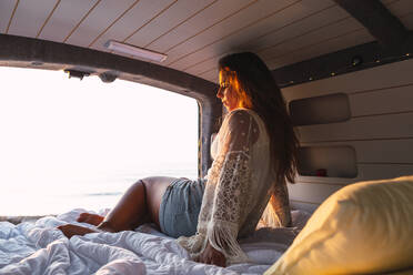 Woman sitting in camper van during sunset at beach - DCRF00995