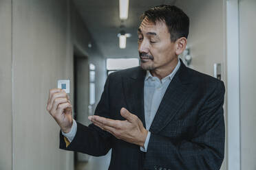 Business man showing computer chip while standing at clinic corridor - MFF06302