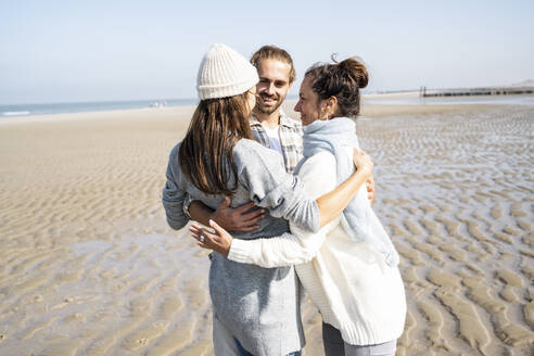 Couple and mother standing with arm around at beach - UUF21674