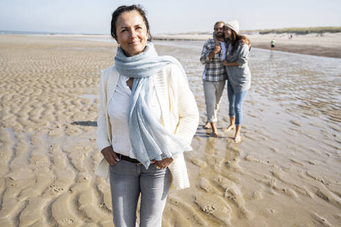 Mature woman looking away while standing with couple in background at beach - UUF21683