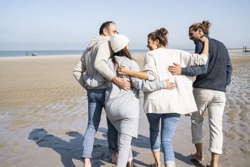 Family with arms around each other walking at beach - UUF21698