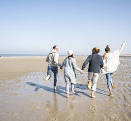 Playful family holding hands while running at beach - UUF21719