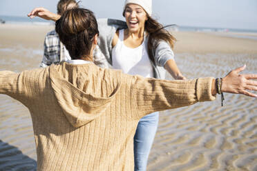Mother standing with arms outstretched to hug daughter with man in background at beach - UUF21728