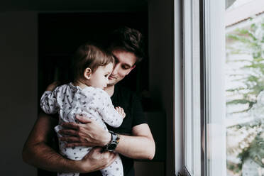 Father holding son while looking through window at home - EBBF00888