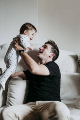 Cheerful father picking up son while sitting on sofa at home - EBBF00897