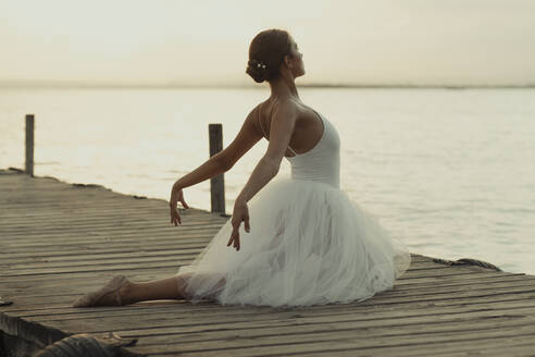 Full body flexible classic ballet female dancer in elegant white dress performing sensual pose on wooden pier against blurred sea in summer evening - ADSF16695