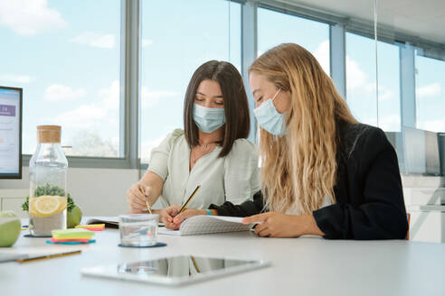 Positive young female colleagues in medical masks for coronavirus prevention taking notes in notebook and discussing details of business project while having meeting in contemporary workspace - ADSF16713