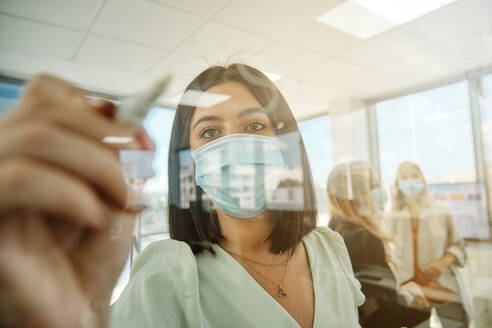 Young female member of business team in protective mask taking notes on glass wall while working with colleagues and searching for solution of business problem in contemporary office - ADSF16719