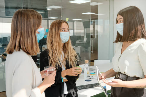 Group of modern young female colleagues in protective masks gathering in contemporary workspace and discussing business ideas while working together during coronavirus pandemic - ADSF16728