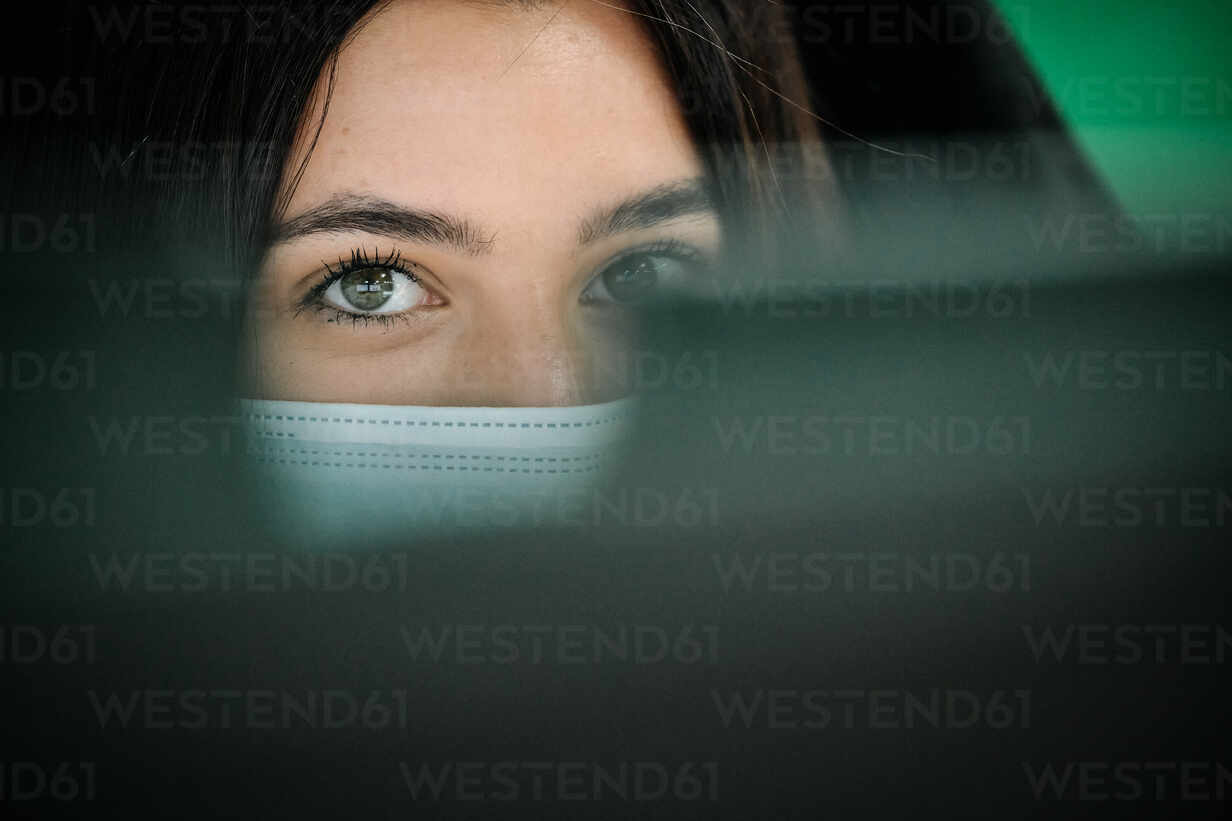 Focused female office employee in protective mask using computer while working in modern office during coronavirus pandemic - ADSF16731 - ADDICTIVE STOCK CREATIVES/Westend61