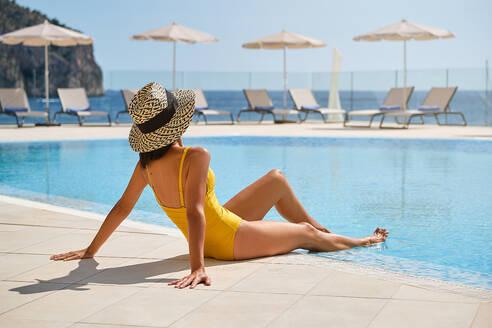 Full length of slim female traveler in swimwear and hat sunbathing at poolside and enjoying sunny day while spending summer holidays in resort - ADSF16746