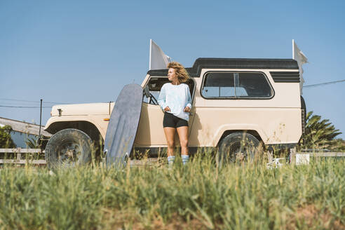 Young Afro woman looking away while standing with surfboard against old off-road vehicle on sunny day - DAMF00569