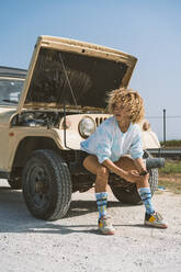 Young blond Afro woman looking away while sitting on bumper of broken-down vehicle during sunny day - DAMF00575