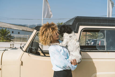 Young blond Afro woman carrying dog while standing by old off-road vehicle on sunny day - DAMF00578