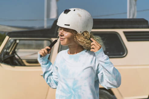 Afro blond woman wearing helmet against vehicle on sunny day - DAMF00581