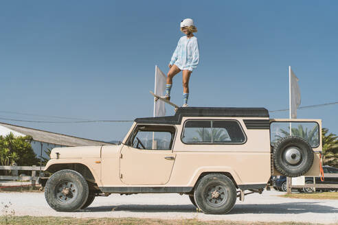 Young woman wearing helmet standing with skateboard on old off-road vehicle against blue sky during sunny day - DAMF00584