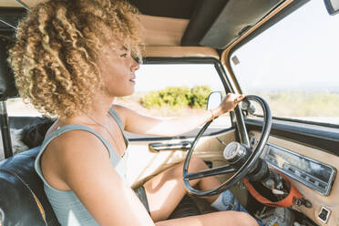 Young blond Afro woman sitting in old off-road vehicle - DAMF00587