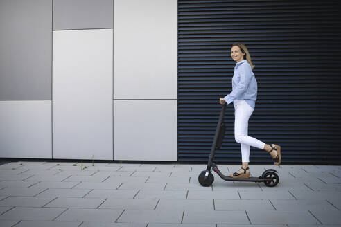 Mid adult woman driving electric push scooter on footpath by metal wall - HMEF01115