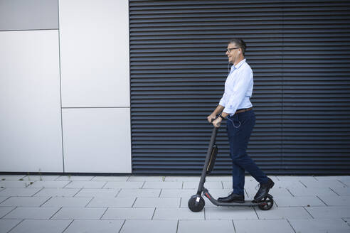 Businessman listening music through earphone standing on electric push scooter - HMEF01121