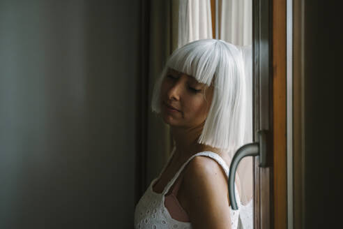 Young woman with eyes closed leaning on window at home - AFVF07339