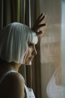 White hair woman looking through window while standing at home - AFVF07342