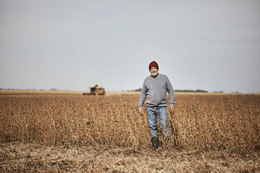 Farmer standing in soybean farm against clear sky - ZEDF03963