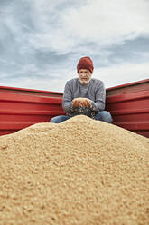 Farmer holding soybean in hand while sitting in tractor against sky - ZEDF03975