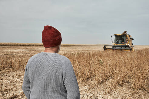 Farmer looking at tractor harvesting crop while standing at farm - ZEDF03981