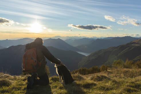 Hiker kneeling while stroking dog at mountain peak during sunset - MCVF00630