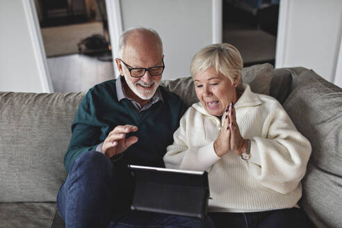 Smiling senior couple using digital tablet while sitting on sofa in living room - MASF19995