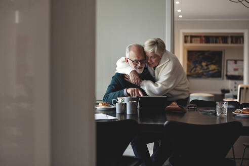 Smiling senior woman embracing partner by dining table in living room - MASF20004
