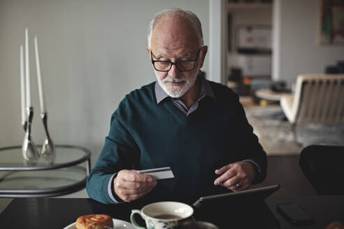 Wrinkled man holding credit card by digital tablet while sitting at dining table in living room - MASF20007
