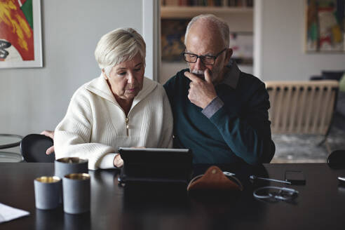 Senior couple using digital tablet while sitting by dining table in living room - MASF20013