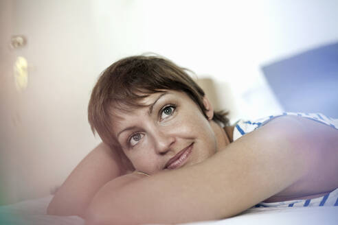 Thoughtful woman looking away while lying down in bedroom at home - AJOF00308